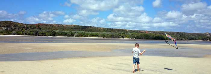 picture of child flying kite at beach